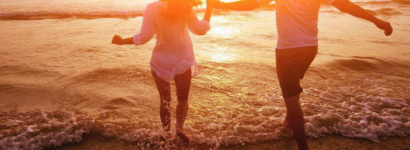 casal que se alimenta de dieta mediterrânea corre de mãos dadas para o mar