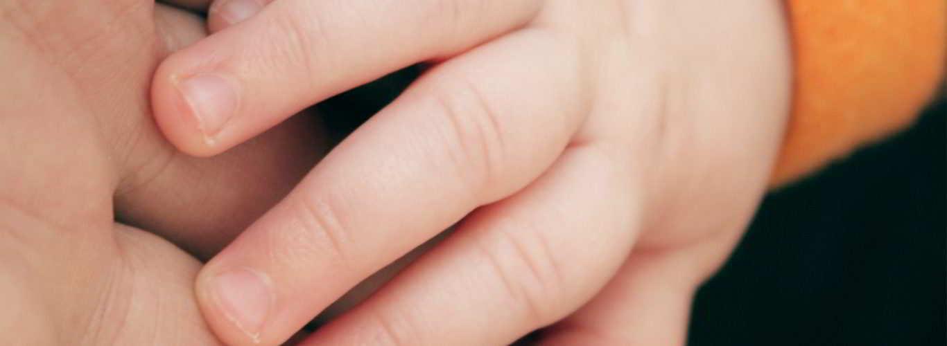 mão de pai e bebê que nasceu livre de doença hereditária