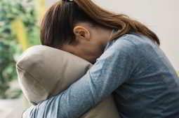 Imagem de mulher abraçando o travesseiro triste pela infertilidade sem causa aparente